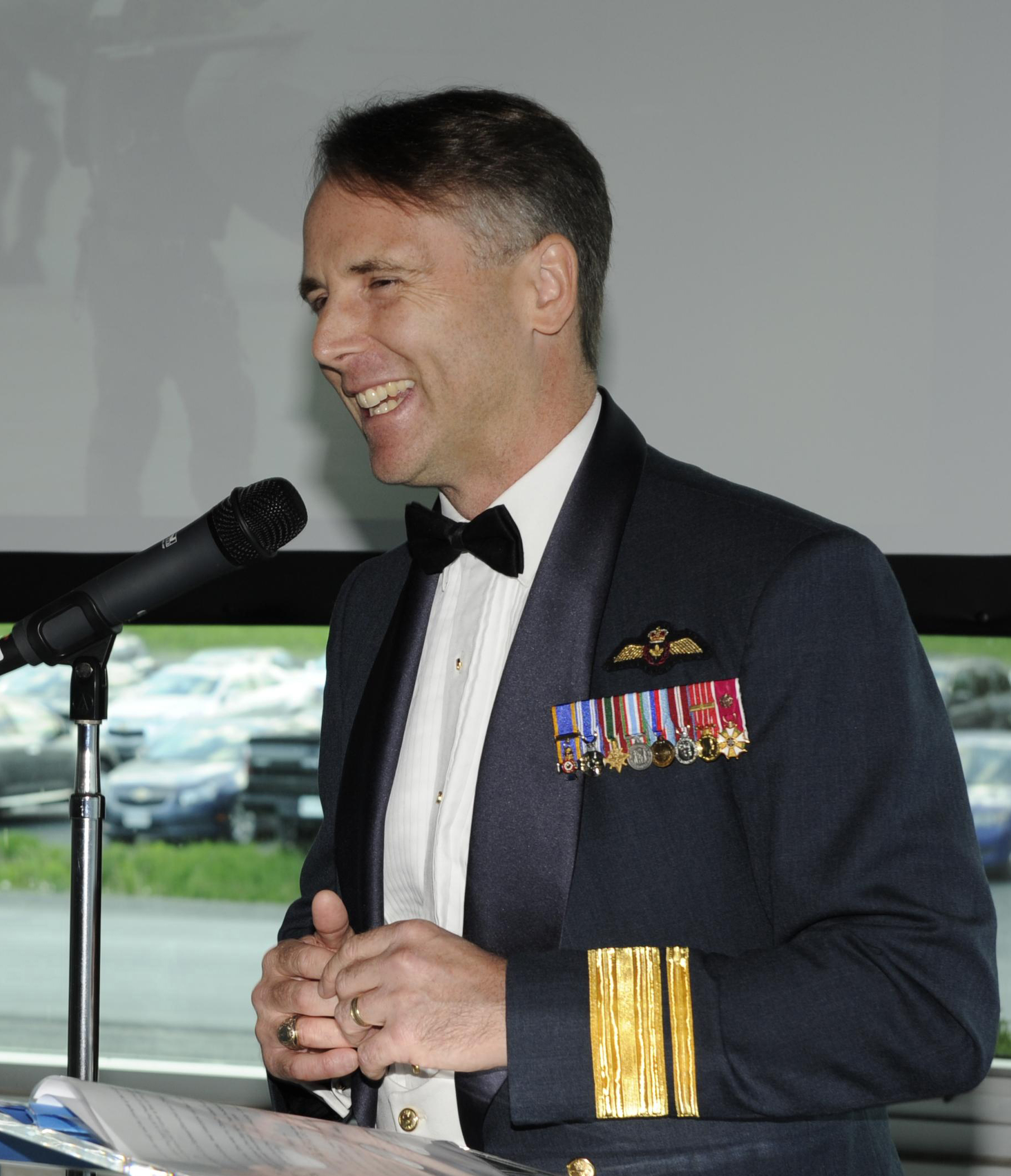 "Major-General Meinzinger, deputy commander of the Royal Canadian Air Force and former commanding officer of 403 Helicopter Operational Training Squadron, addresses current and former ""Wolfpack"" members at the squadron's 75th anniversary dinner, held May 27, 2016, in Gagetown, New Brunswick. On May 4, 2018, now-Lieutenant-General Meinzinger took command of the Royal Canadian Air Force. PHOTO: DND"