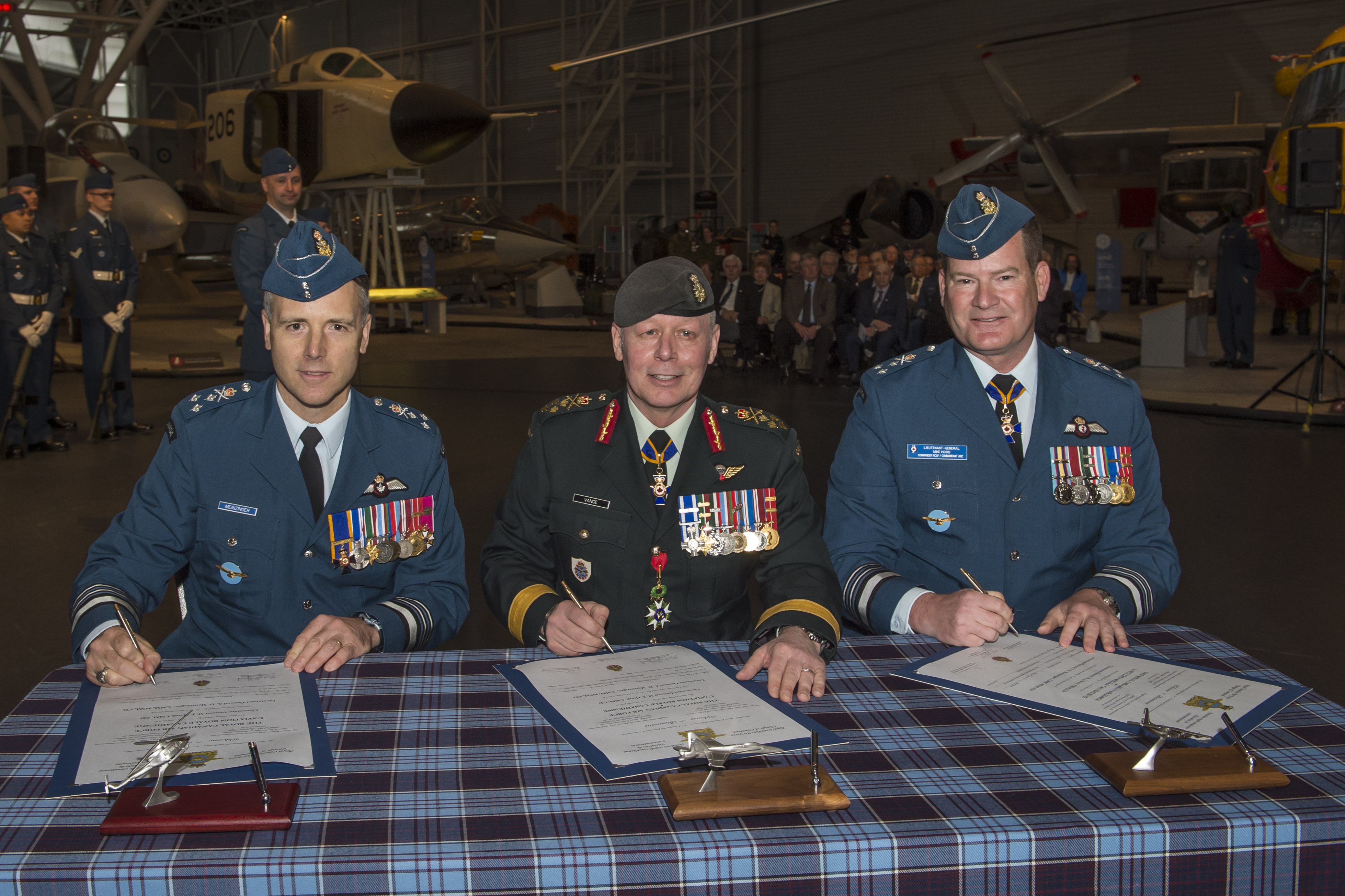Three men in military uniforms sit behind a tartan-covered table, with documents resting on the table.