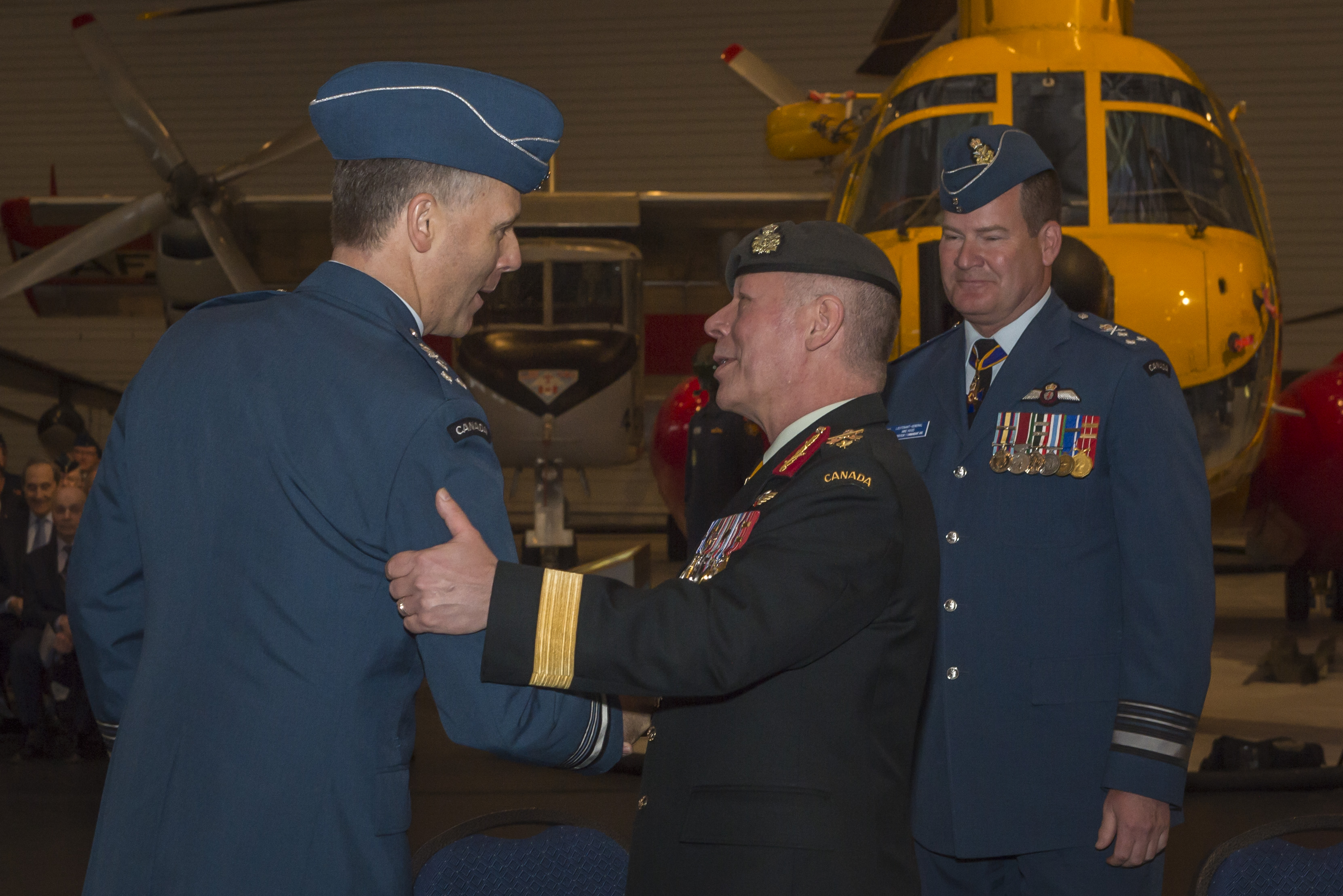 General Jonathan Vance (centre) congratulates Lieutenant-General Al Meinzinger on assuming command of the Royal Canadian Air Force as the former commander, Lieutenant-General Mike Hood looks on. PHOTO: Corporal Alana Morin, FA03-2018-0040-003