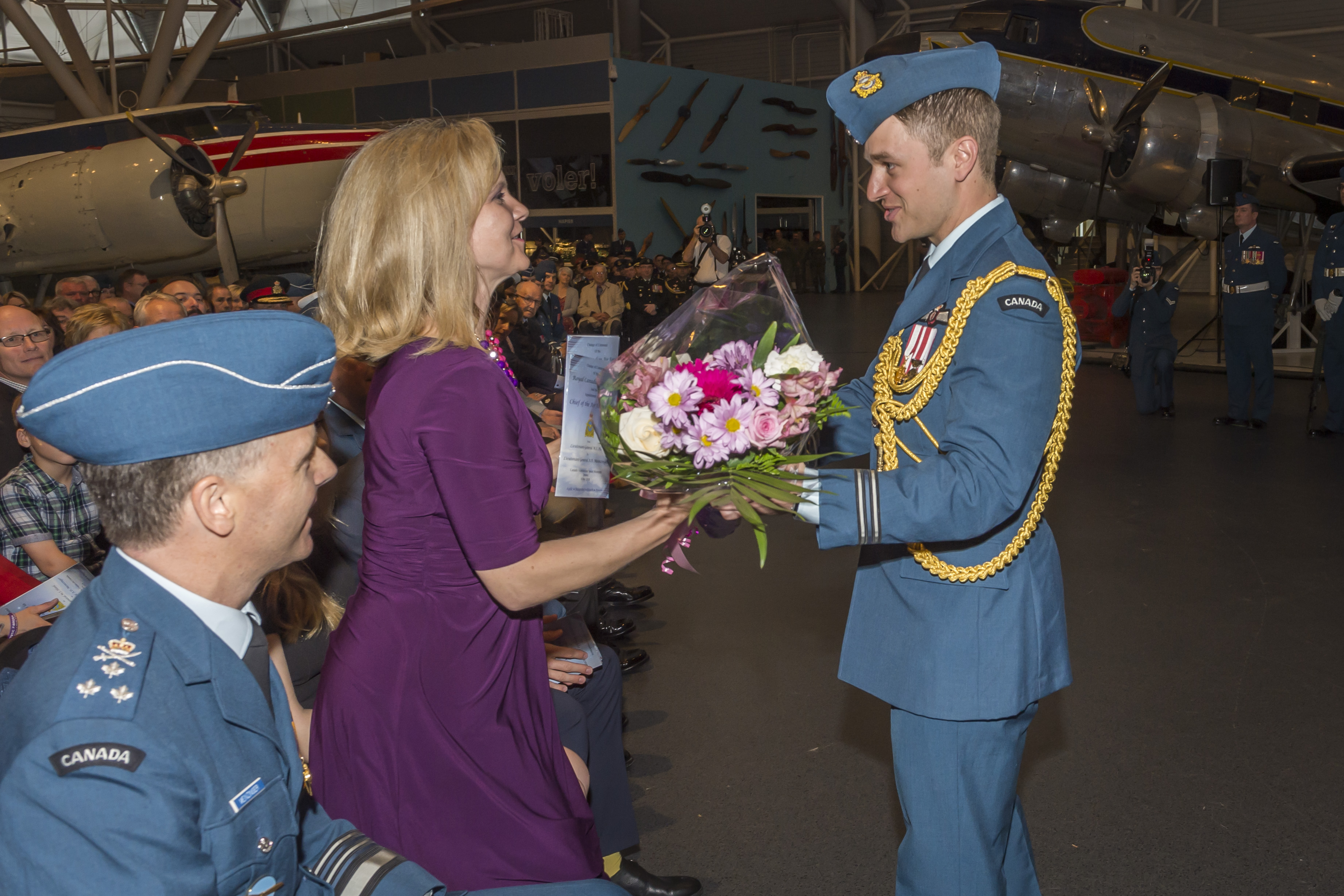 Captain Olivier Dupuis, aide-de-camp, presents Ms. Joy Meinzinger with flowers, welcoming her on behalf of all Air Force personnel, as Lieutenant-General Meinzinger looks on. PHOTO: Corporal Alana Morin, FA03-2018-0040-053