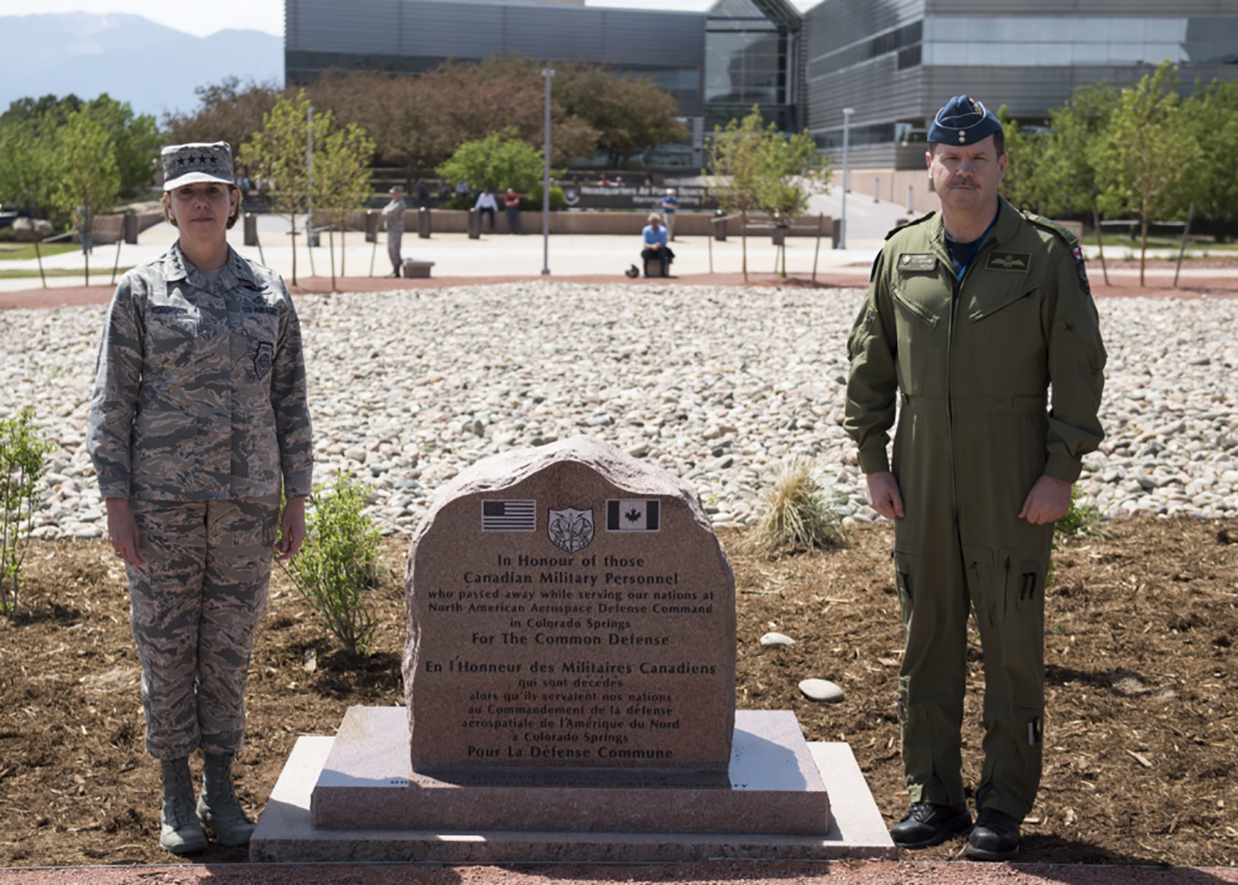 U.S. Air Force General Lori Robinson, Commander of the North American Aerospace Defense Command and U.S. Northern Command, and Canadian Lieutenant-General Pierre St-Amand, NORAD Deputy Commander, pause for a photo during the May 11, 2018, unveiling ceremony for a memorial cairn outside the NORAD and USNORTHCOM headquarters building on Peterson Air Force Base, Colorado. The cairn honors Canadian service men and women who died while serving at NORAD in Colorado Springs. The placement and dedication of the cairn was conducted in conjunction with the 60th Anniversary of NORAD and the Canada/U.S. binational NORAD agreement. PHOTO: U.S. DoD, N&NC Public Affairs