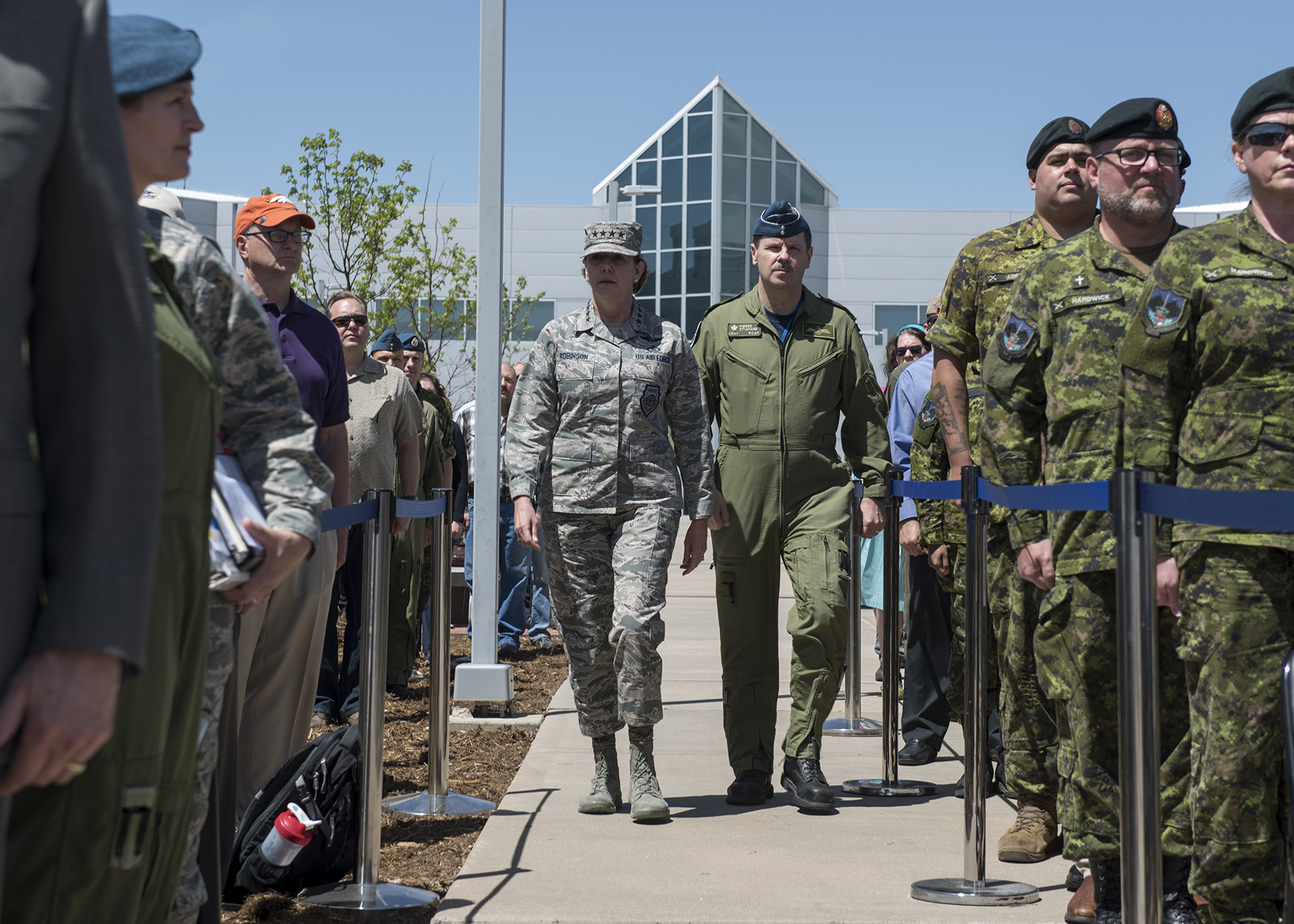 U.S. Air Force General Lori Robinson, Commander of the North American Aerospace Defense Command, and U.S. Northern Command and Canadian Lieutenant-General Pierre St-Amand, the NORAD Deputy Commander, approach for the ceremony to unveil a memorial cairn outside the NORAD and USNORTHCOM headquarters building on Peterson Air Force Base, Colorado, on May 11, 2018. The placement and dedication of the cairn was conducted in conjunction with the 60th Anniversary of NORAD and the U.S. Canadian binational NORAD agreement. PHOTO: U.S. DoD, N&NC Public Affairs