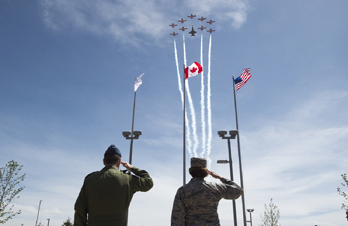 slide - A man and a woman, both in uniform, stand and salute flags as a formation of 10 aircraft flies overhead.