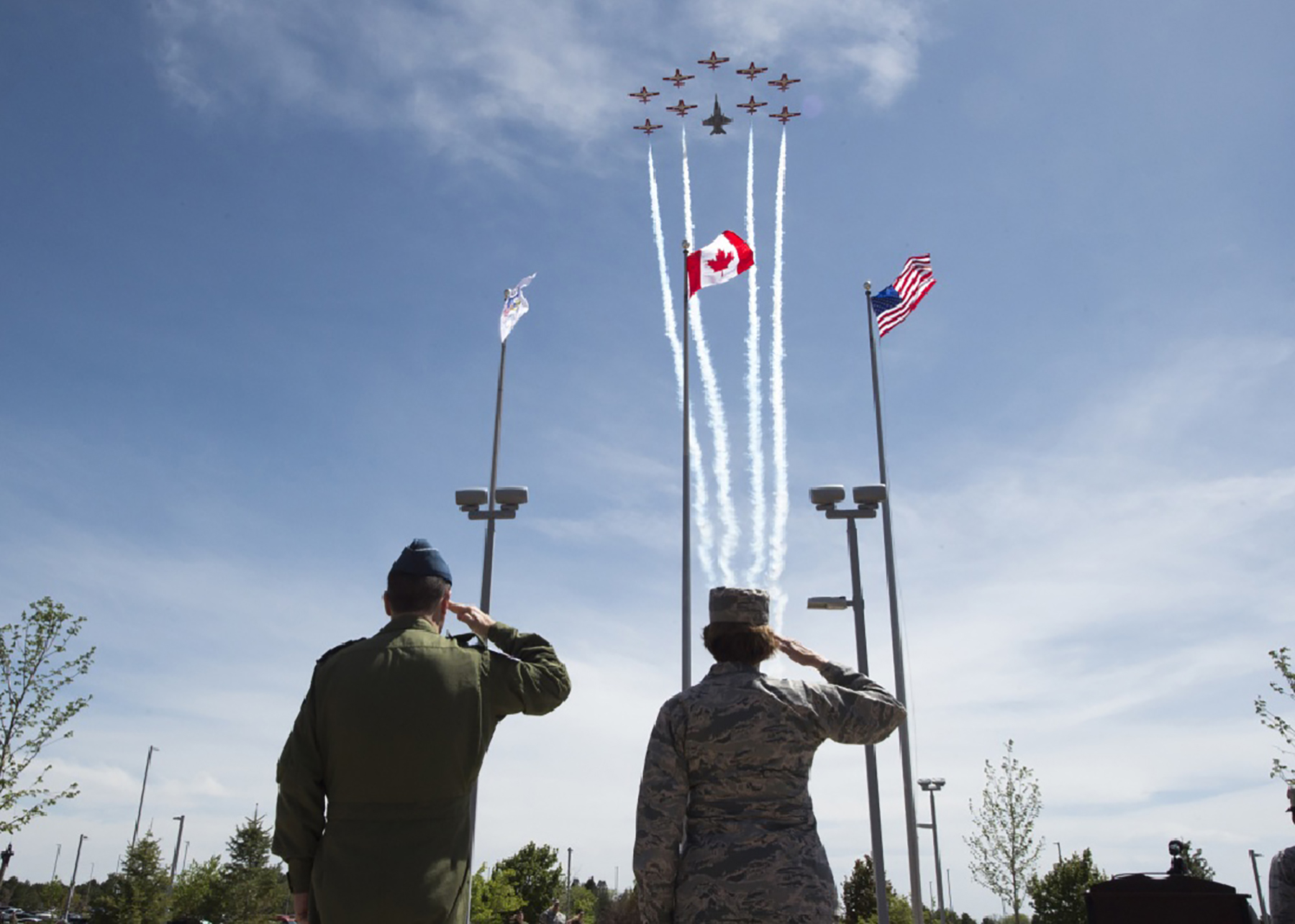 A man and a woman, both in uniform, stand and salute flags as a formation of 10 aircraft flies overhead.