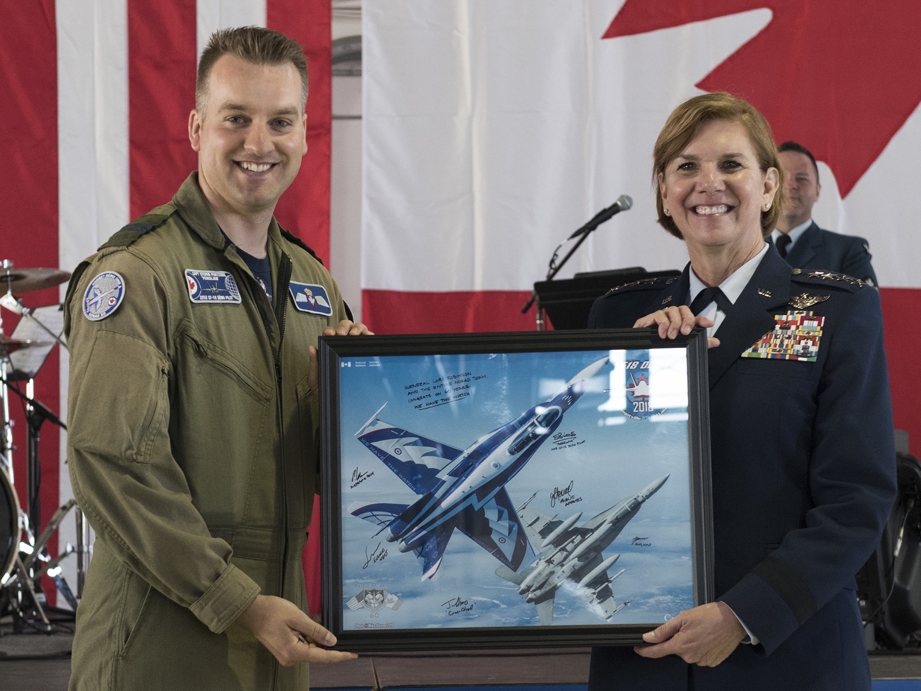 "On May 12, 2018, during the celebration of NORAD's Diamond anniversary at Peterson Air Force Base in Colorado, Captain Stefan Porteus, pilot of the RCAF's 2018 CF-18 Demo Jet, presents a lithograph to General Lori J. Robinson, commander of NORAD/US NORTHCOM. The litho portrays the Demo Jet, which is painted in a design honouring the anniversary. ""Diamond"" comes from the Greek ""adamas"", meaning unconquerable, enduring. PHOTO: U.S. DoD, Staff Sergeant Emily Kenney"