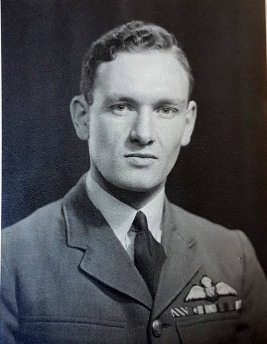A head and shoulders photo of a man wearing a military tunic with tie. Near his left lapel are wings and several military medal ribbons.