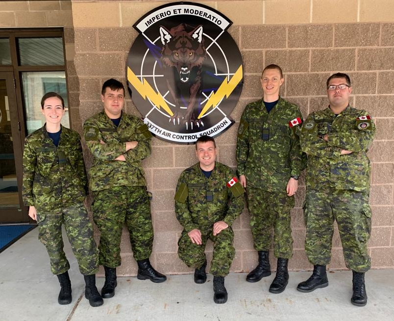 Five people wearing Canadian disruptive pattern combat uniforms stand in a row.