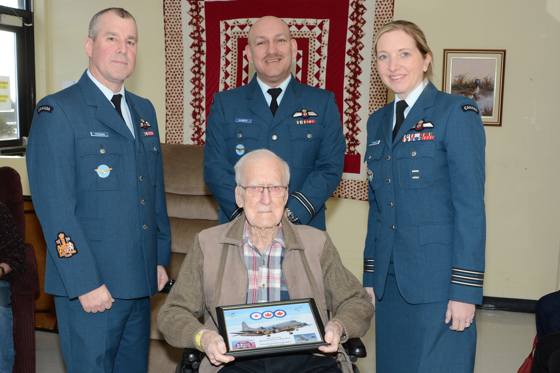 Three people, two men and a woman, all wearing blue Air Force uniforms, stand behind an elderly man in a wheelchair wearing civilian clothes and holding a framed picture.